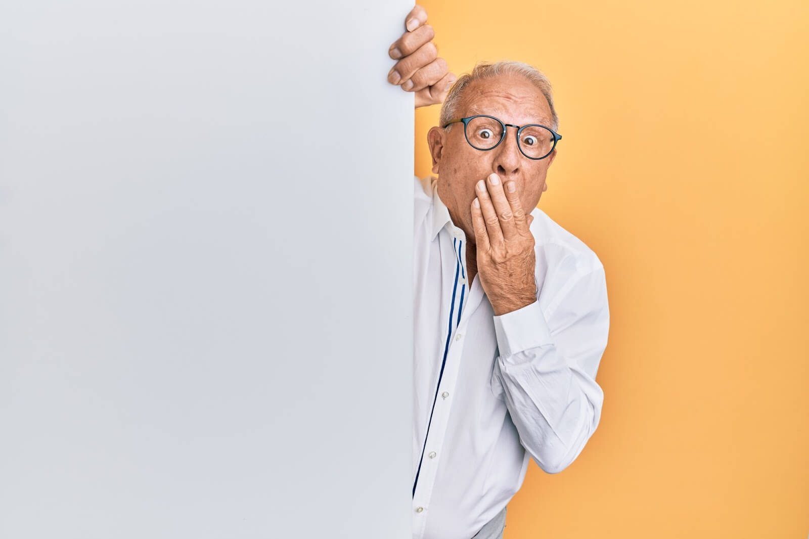 a male senior covering his mouth with one hand in shock