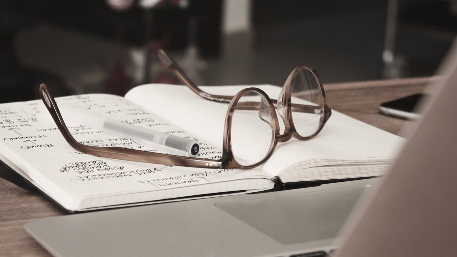 glasses sitting on a pile of documents